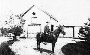 Mr. Allen On A Horse In Front Of The Original Barn